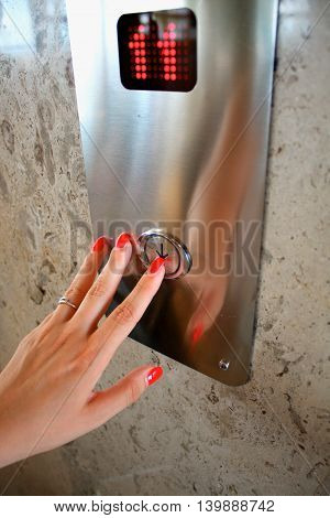 Female hand pressing elevator down button .