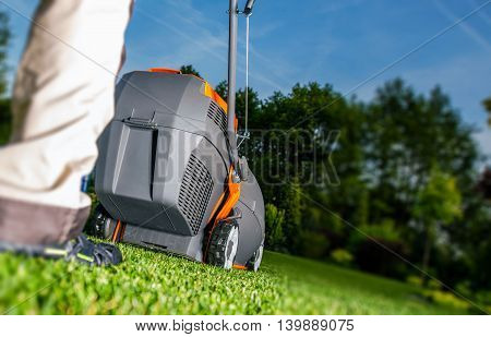 Summer Lawn Mowing and Backyard Landscaping. Men with Grass Mower.