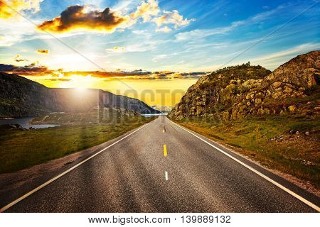 Norway highway in the mountains at sunset.