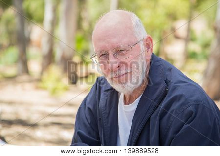 Happy Content Senior Man Portrait Outdoors At Park.