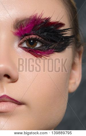 beauty creative makeup with feathers on eyes macro closeup