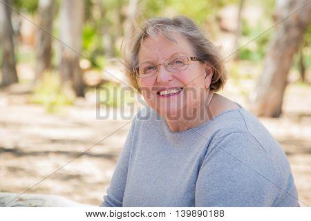 Happy Content Senior Woman Portrait Outdoors At Park.