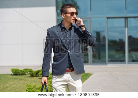 Full length portrait of a confident young businessman walking in the city talking on cell phone
