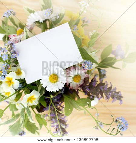 ordinary bouquet of flowers with a clean card for inscriptions and chamomile / a note by in a bouquet of flowers