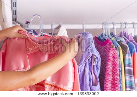 Young Woman Choosing Red Dress On A Rack In A Showroom