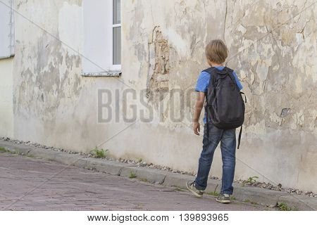 Boy with backpack. Schoolboy walking in the street. Back view. People education, back to school, travel, leisure concept