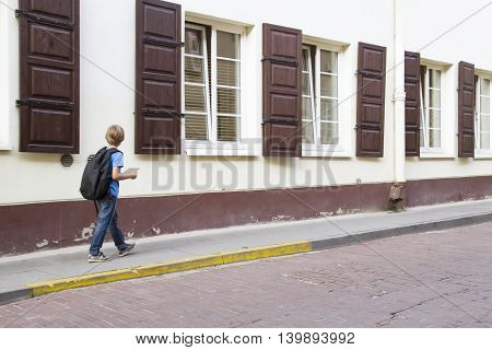Boy with backpack. Schoolboy ot tourist in the street. Back view. People education, back to school, travel, leisure concept