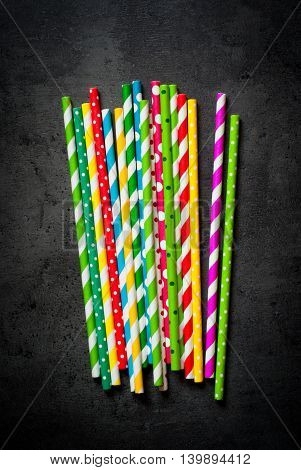 Multi-colored straws against a black background.View from above with copy space.
