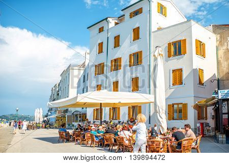Piran, Slovenia - May 7, 2016: Crowded coastline with people sit at the cafe in Piran town. Piran is one of Slovenia's major tourist attractions.