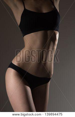 silhouette of slim woman body in black lingerie low key