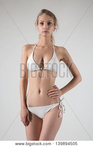 Pretty woman in white lingerie looking at camera in studio