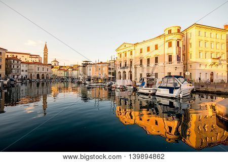 Piran, Slovenia - May 8, 2016: Piran old town center with church tower and marina at the morning. Piran is one of Slovenia's major tourist attractions.