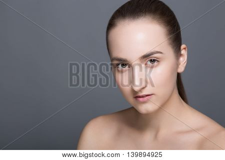 Beauty fashion vogue style face of caucasian brunette with elegant make-up, blue eyes, natural lips touching perfect skin. Close-up studio portrait isolated. Black background with grey spot. Toned.