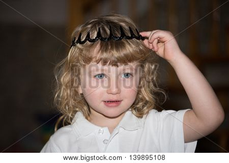 The charming little boy with blue eyes and blond curls in toy crown