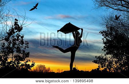 Young Girl Silhouette With Shawl Dancing On Blue And Golden Cloudy Sunset Background