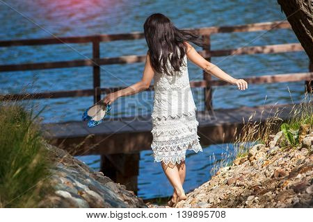 Girl in a white dress going down to the river