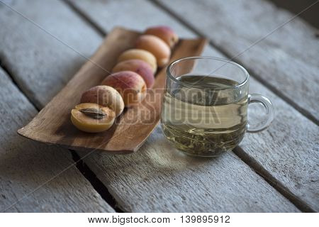 Peaches on a wooden stand and green tea in a transparent Cup