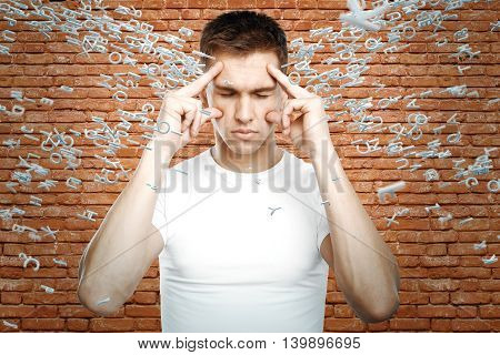 Brainstorm concept with thoughtful young guy surrounded with abstract letters on red brick wall background