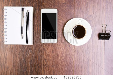 Top view of wooden office desktop with spiral notepad other stationery items blank smartphone and coffee cup. Mock up