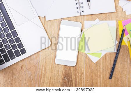 Top view of messy wooden desktop with blank white cellphone laptop keyboard spiral notepad colorful stickers and other office tools. Mock up