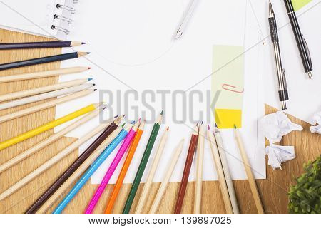 Closeup of colorful pencils pens paper sheets notepad stickers and plant on wooden desktop