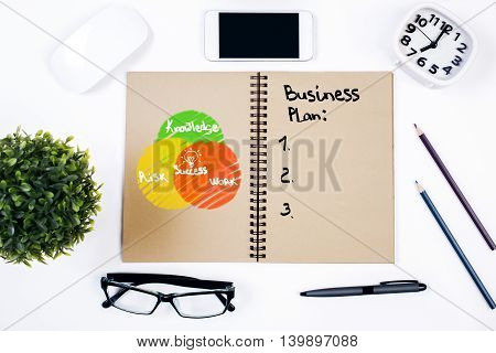 Top view of spiral notepad with unfinished business plan and success chart placed on white office desktop with various objects