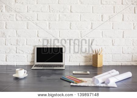 Blank laptop screen on wooden desktop with coffee cup pencils paperwork and other items on white brick background. Mock up