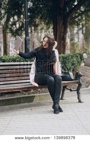 beautiful young model sitting on a bench and posing