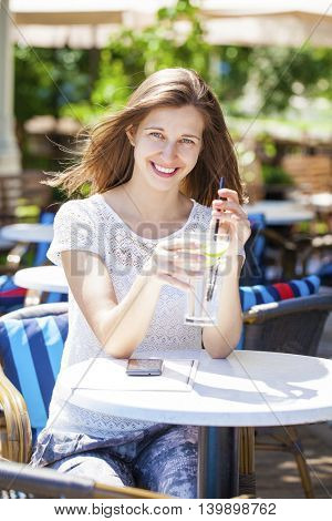 Young beautiful brunette woman with a cold drink sitting in a cafe on the street