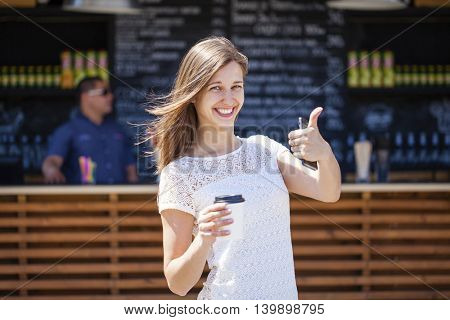 Young beautiful woman with a paper cup on the background of coffee, summer outdoors