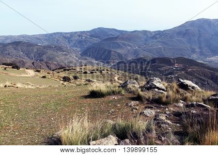 Sierra Nevada Mountains. Spring. The slopes of the valley are covered with dry bushes and grass, large rocks and moss. Nature Spain