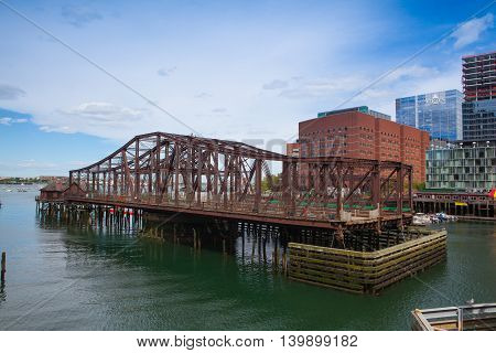 BOSTON,MASSACHUSETTS,USA - JULY 2,2016: Boston skyline and Northern Avenue Bridge. Built in 1908 it was closed to vehicle traffic in 1999