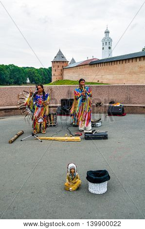 VELIKY NOVGOROD RUSSIA - AUGUST 9 2015. American Indians in traditional outfits perform music in the center of Veliky Novgorod
