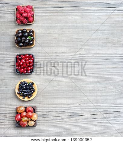 Raspberry Bilberry Gooseberry Cranberry and Currant on wooden background. Top view high resolution product.