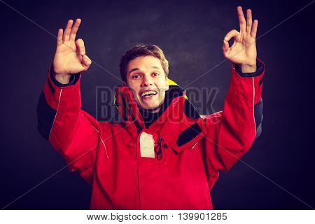 Smiling man making gestures. Young male in weatherproof oilskin. Adventure endurance outdoors concept.