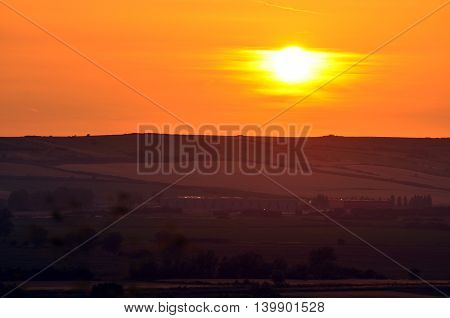 Sunset above the field with orange clouds