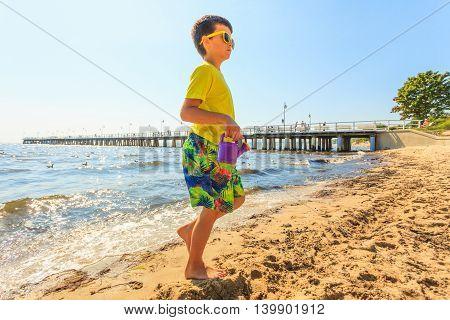 Boy Walking On Beach.