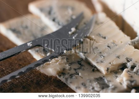 Blue cheese close up on an old wooden board and a knife Selective focus and shallow Depth of field