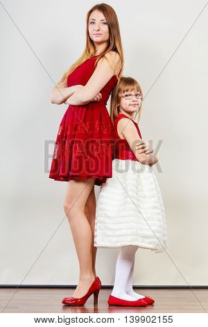 Family relationships. Beauty mother with lovely daughter spending time together. Mommy and girl child wearing dress.