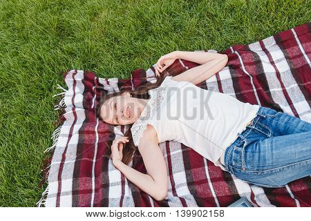 Young Woman with Long Hair Lying on the Grass