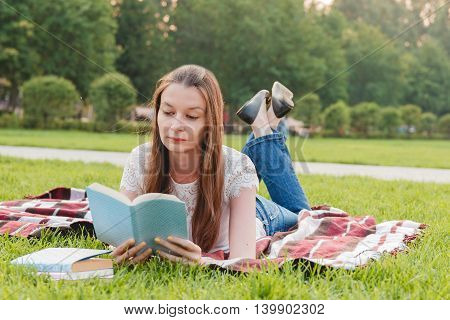 Young Woman Reading Book at Park Lying on Grass. Education Concept