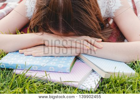 Girl Tired of Studying and Lying with Books on Green Grass. Education Concept
