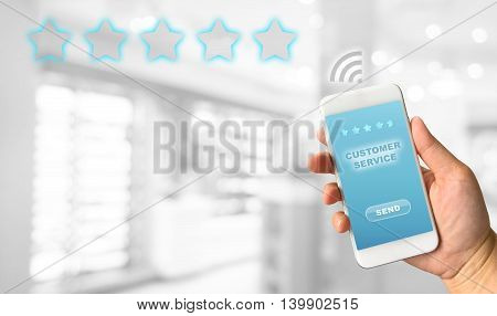 Woman hand holding smartphone against white grey bokeh abstract background customer service concept