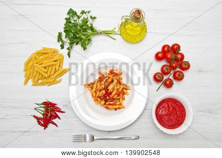 dish with penne and arrabbiata sauce on white wood
