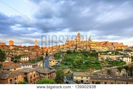 Siena sunset panoramic skyline. Mangia tower and Cathedral Duomo landmark. Tuscany Italy.