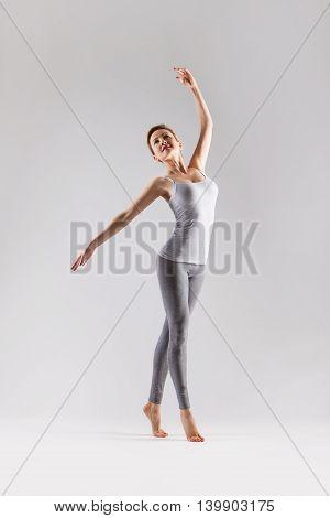 Sporty beautiful ballet dancer woman posing on a studio