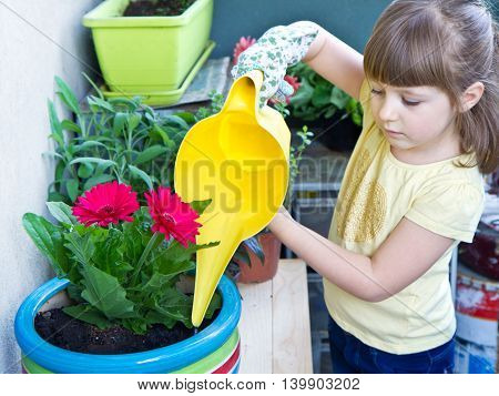 Young girl watering potted flower plant smiling