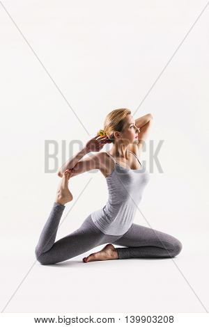 Sporty attractive young beautiful woman doing yoga on a studio background