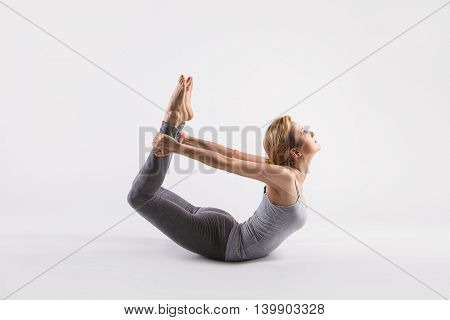 Sporty attractive young beautiful yoga posing on a studio background. Model doing Dhanurasana, Bow Pose. Full length.