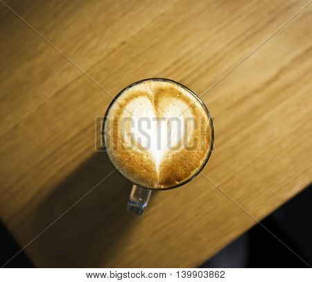 A cup with cappucino on wooden table